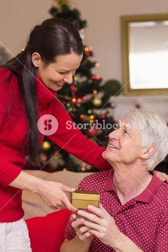 Mother offering gift to grandfather