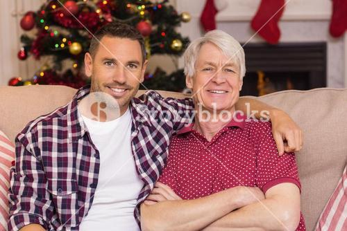 Father with arm around grandfather posing on sofa