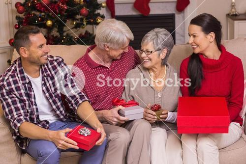 Happy family with gift on the couch