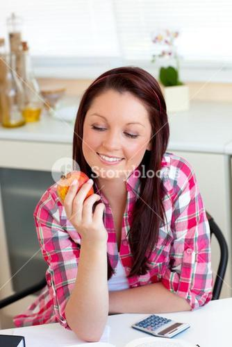 Smiling woman holding an apple sitting in the kitchen