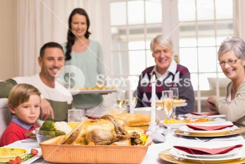 Woman holding christmas dinner with family at dinning table