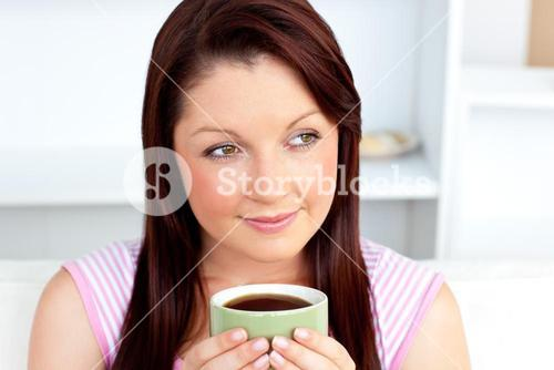 Woman holding a cup of coffee at home