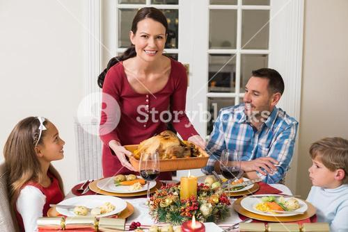 Smiling woman serving roast turkey to her family