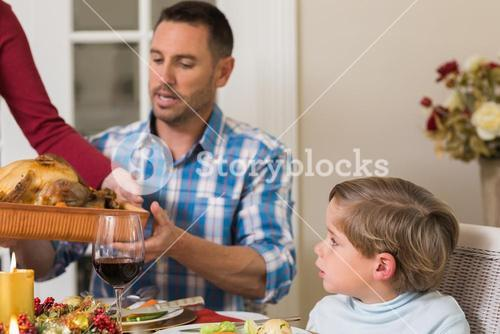 Woman passing the roast turkey to her husband
