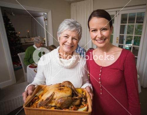 Women posing with roast turkey in front of their family