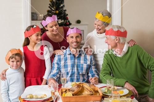 Cheerful extended family in party hat at dinner table
