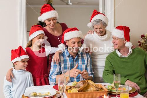Happy extended family in santa hat at christmas dinner