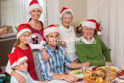 Happy extended family in santa hat looking at camera