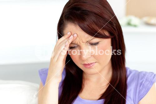 Woman with a headache sitting on a sofa at home