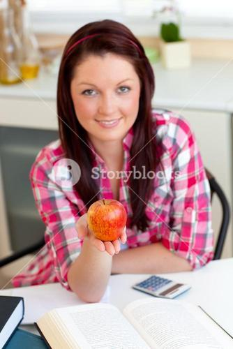Serious woman holding an apple sitting in the kitchen