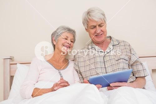 Senior couple relaxing in bed using tablet pc