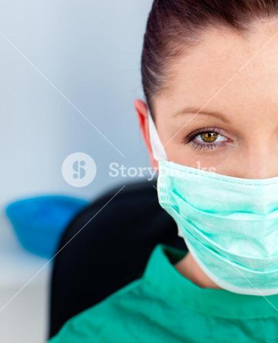Close up of a beautiful female doctor with scrubs sitting in her office