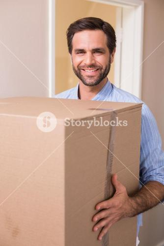 Happy man carrying moving box