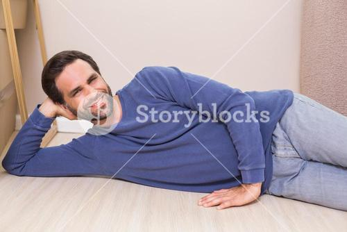 Happy man lying on floor with moving boxes