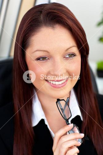 Cute businesswoman holding glasses