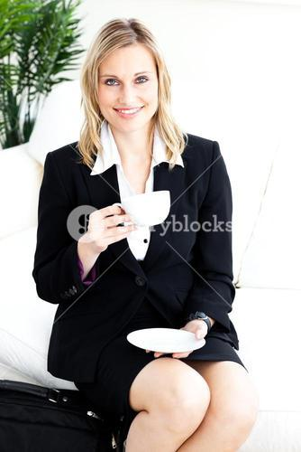 Elegant young businesswoman drinking coffe in the office