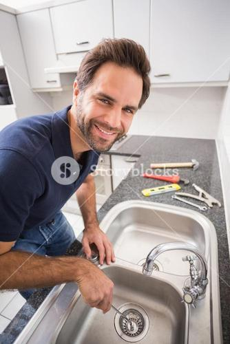 Plumber fixing sink with screwdriver
