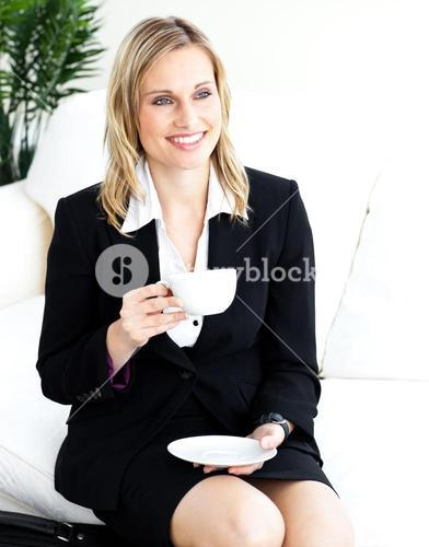 Confident businesswoman drinking coffe in the office sitting