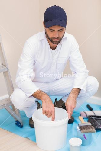 Painter mixing paint in a bucket