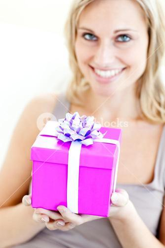 Charming woman holding a present in front of her