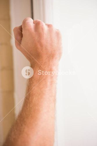 Hand knocking at the door