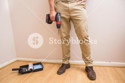Construction worker holding power tool