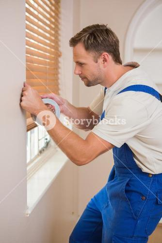 Man puting silver duct tape on the corners of the wall