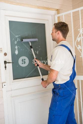 Handyman cleaning the window with squeegees
