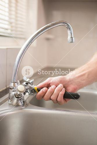 Man fixing tap with pliers