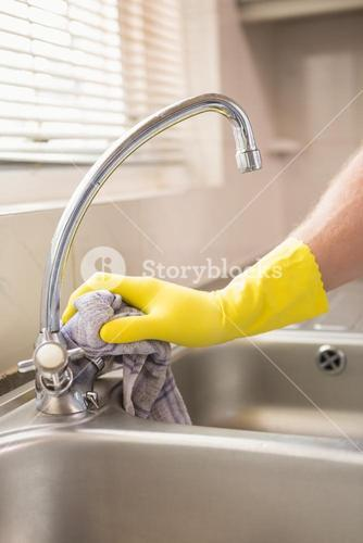 Hand cleaning a sink with cloth