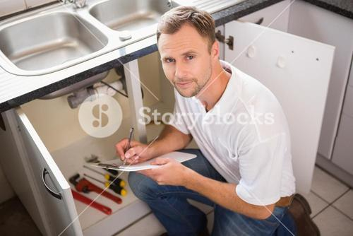 Plumber crouching and taking notes