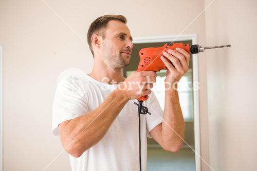 Construction worker drilling hole in wall