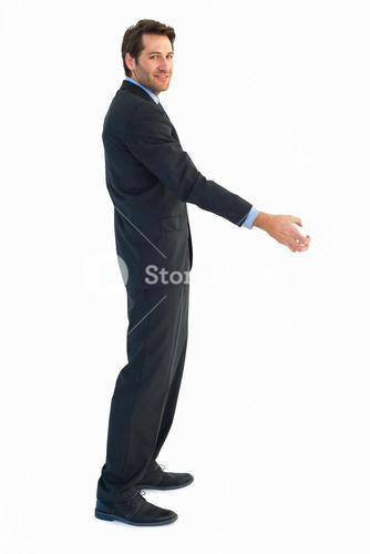 Smiling businessman reaching out to shake hands