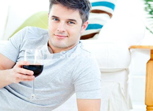 Charming man holding a wineglass in the livingroom