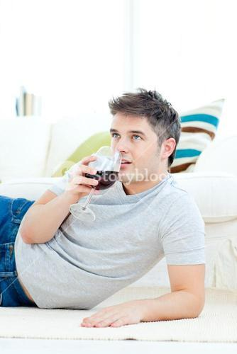 Positive young man drinking wine in the livingroom