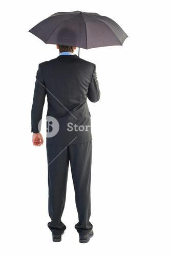 Rear view of businessman sheltering with umbrella