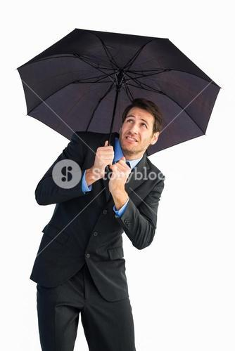 Businessman sheltering with black umbrella