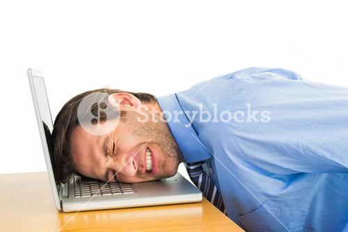 Businessman resting head on keyboard