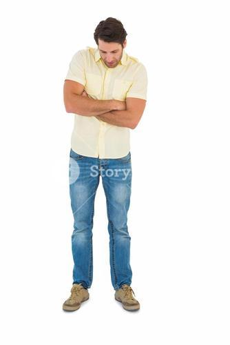 Handsome man standing looking down with arm crossed