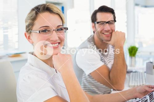 Photo editors smiling to the camera with hands under chin