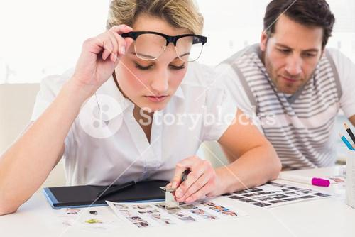 Editor using magnifying loupe to view the contact sheet