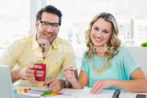 Interior designer drinking coffee at desk