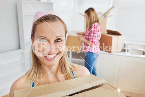 Two positive women carrying boxes at home