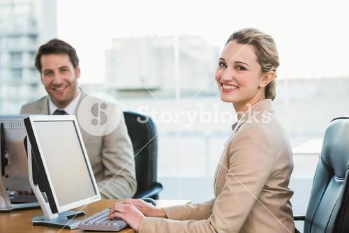 Two young business people using computer