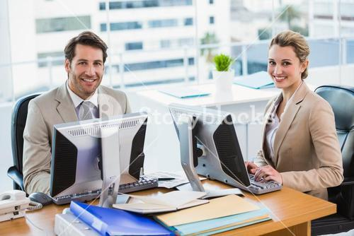 Business people using computer while looking at camera