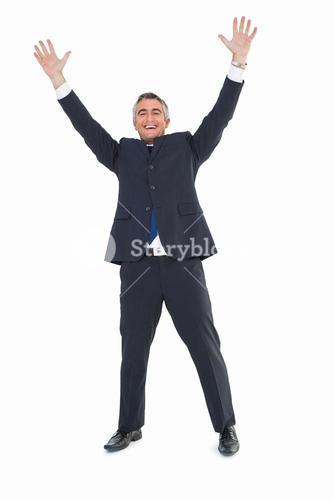Happy businessman in suit with arms up