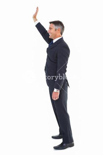 Happy businessman well dressed waving