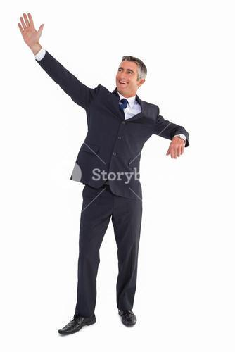Happy businessman standing and waving