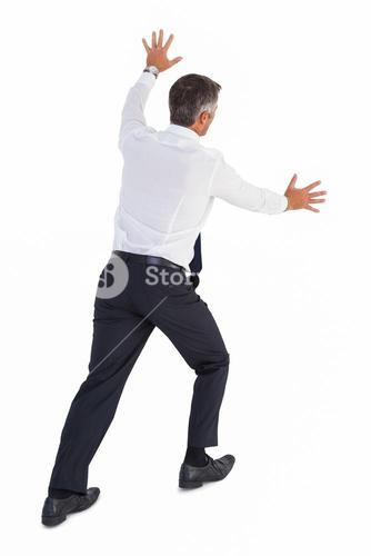 Businessman standing and pushing a wall
