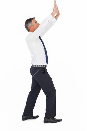 Businessman in suit looking up and pushing